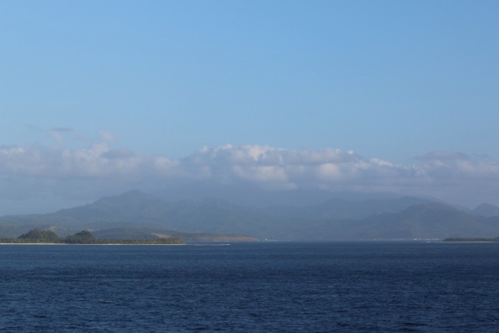 The coast of Luzon.  In the clouds is the peak of an active volcano, Busayan.