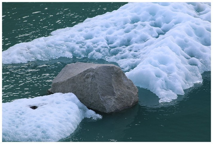 Amazingly, this large rock, carved by the glacier, is still sitting atop the calved iceberg