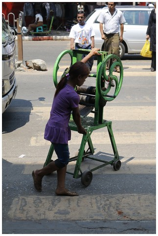 A young girl pushing a laundry mangle along the street