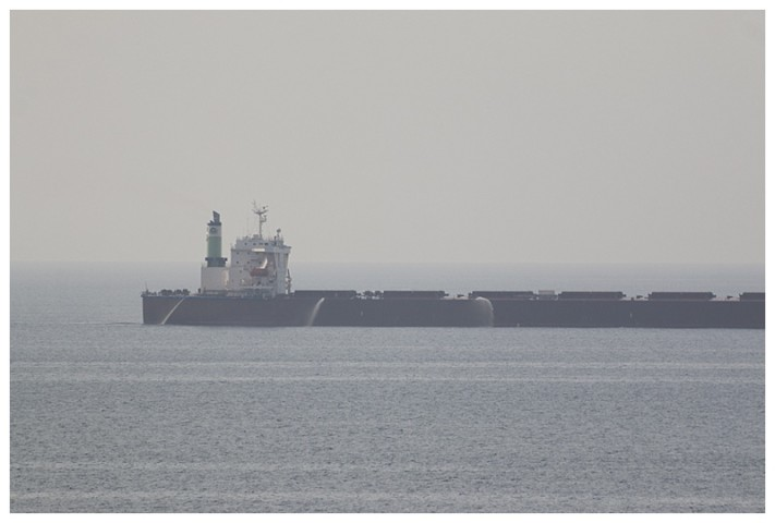 Passing a slow bulk-carrier; she has her fire hoses running as a deterrent.  I have seen others, using their ballast tanks, overflowing the side with a waterfall down their entire length.  Nowadays many of them carry the best deterrent of all, armed security personnel.
