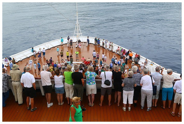 Guests on our foredeck and deck 6 watch Polynesian dancers, (who have sailed with us) as we approach the bay