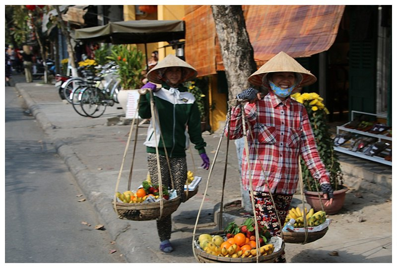 Vegetable and fruit sellers carrying their wares