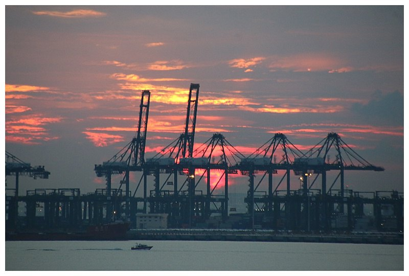 It soon clears and a beautiful sunset behind Portainer cranes on the distant terminal
